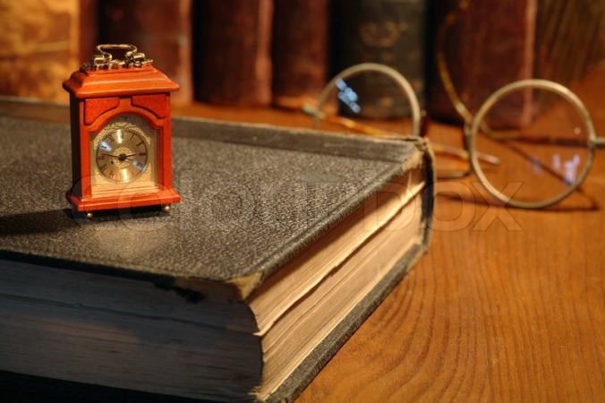 1617345-vintage-still-life-small-wooden-clock-standing-on-old-book-on-background-with-books-and-spectacles