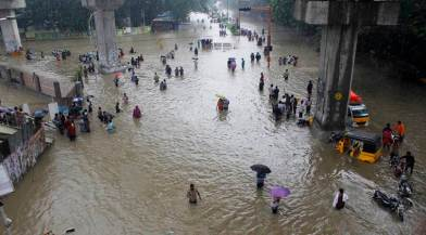 People wade through a flooded road in Chennai, Tamil Nadu, India, Wednesday, Dec. 2, 2015. Weeks of torrential rains have forced the Chennai airport in southern India to close and have cut off several roads and highways, leaving tens of thousands of people stranded in their homes, government officials said Wednesday. (AP Photo)